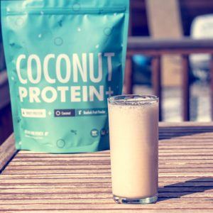 A glass of Organic Whey Coconut Protein+ mixed with milk and goji powder